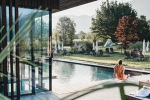 Mann sitzt am Pool am Hotel in den Alpen