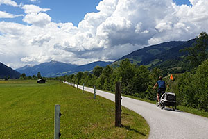 Mann unterwegs mit Kind auf Fahrrad und Kinderanhänger mit Wind- und Wetterschutz ©zweiradkraft.com