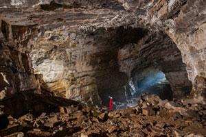 Mann steht in der Grotte von Postojna in Slowenien
