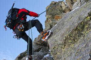 Mann hängt draußen an einer Kletterwand