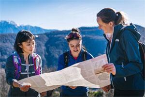 Frauen orientieren sich in der Bergwelt an einer Landkarte