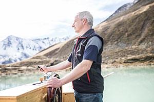Mann am Steuer eines Floßes am Riffelsee in Österreich
