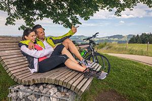 Paar mit Fahrrad macht Pause auf einer Bank