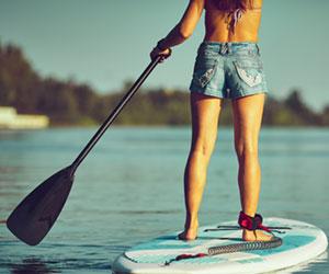 Frauenbeine von hinten auf Stand-up-Paddel