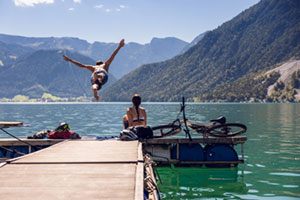 Ein Man springt in den See, die Frau sitzt am Steg
