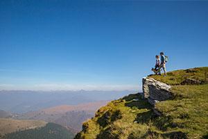 2 Menschen und ein Hund stehen in der Bergwelt der Schweiz