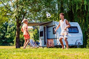 Mann und Sohn spielen Fußball vor einem Wohnmobil