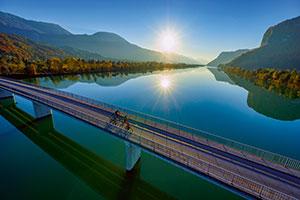 Radler überqueren eine Brücke auf dem Donauradweg in Kärnten