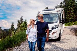 Paar steht lächelnd vor einem Wohnwagen in schöner Landschaft