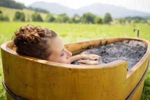 Frau sitzt im Moorbad vor Alpenkulisse