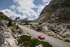 Rotes Auto fährt durch die Dolomiten-Landschaft in den italienischen Alpen
