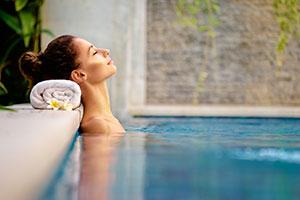Eine Frau entspannt sich im Pool einer Therme