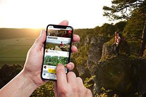 Ein Paar wandert und sammelt mit seinem Smartphone Punkte, mit denen es später belohnt wird ©Top Trails of Germany