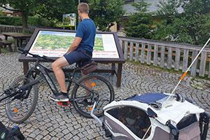 Ein Mann ist mit Moutnainbike und Fahrradanhänger mit Kind unterwegs ©zweiradkraft.com